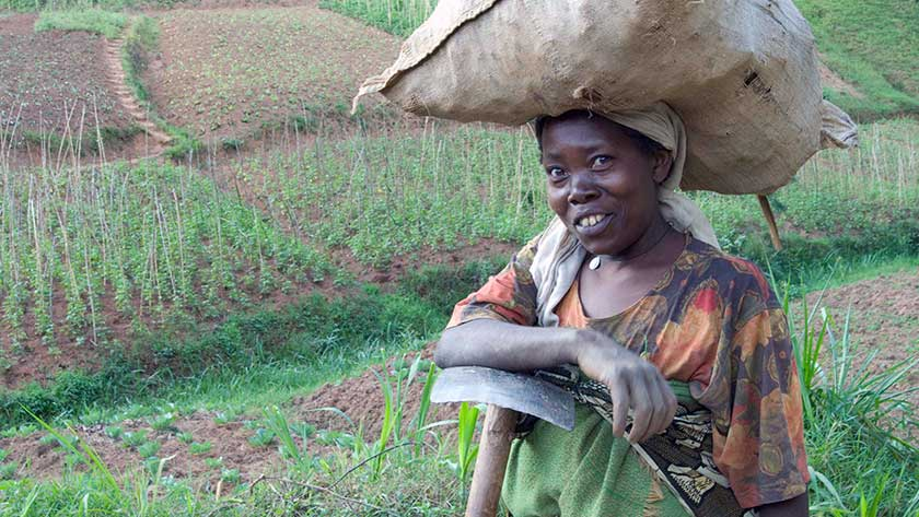 A farmer in Rwanda standing in front of her land.